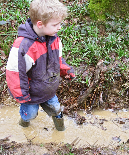 boy wading in muddy water