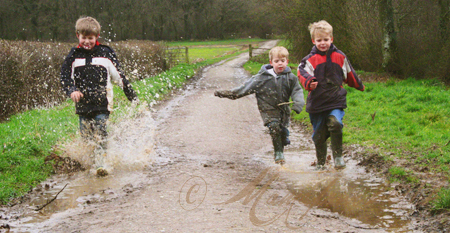 boys running through muddy water
