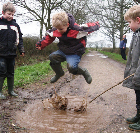 boy high in air over muddy puddle