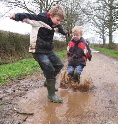 boys splashing in muddy puddles